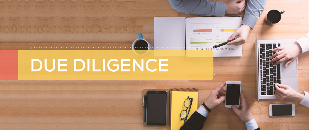 Due Diligence overlaid on a desk with business persons working.