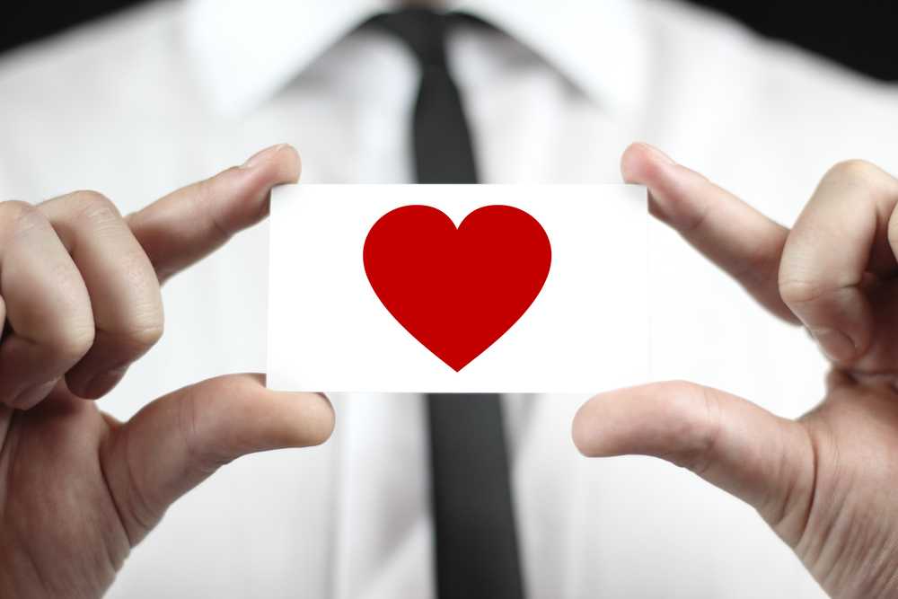 Close-up of business card with heart on it held be a person in a suit seen partially in the background